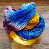 a hank of blue, yellow and purple yarn piled onto itself like a soft serve ice cream. Sitting on a wood background we're looking at it from a side view. we can see where the blue and purple meet the original white color of the yarn shows through.
