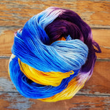 against a wooden background we see a hank of yarn swirled atop itself. Bright sunshine yellow is sandwiched between strands of brilliant sky blue, on the far end of the swirl are the dark purple sections of dyed yarn