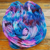 one hank of hand speckled yarn laid out to show the color changes. its speckled randomly wiht colors of blue purple fuchsia magenta pink and pops of white