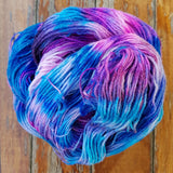 close up of hand speckled yarn in a hank but it's piled up on top of itself. the yarn is speckled in colors of magenta purple fuchsia pink and deep cobalt blue, with little bits of white undyed yarn showing through
