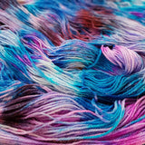 close up image of rolling waves of hand speckled yarn in all sorts of flora colors purple pink magenta fuchsia burgundy blue and white. a little bit os silver sparkly tinsel is visible against some of the darker colors