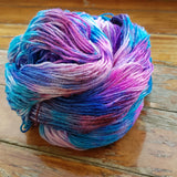 close up of on piled untwisted hank. it looks like a tornado of magentas pinks purples and blues