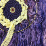 image of woven dream catcher in shades of purple and cream set on a background of yarn in shades of purple and violets