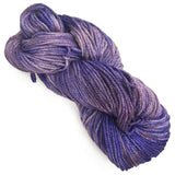 image of one twisted hank of yarn positioned diagonally with a well defined ply. the color of the yarn is in various shades of light purple and dark purple