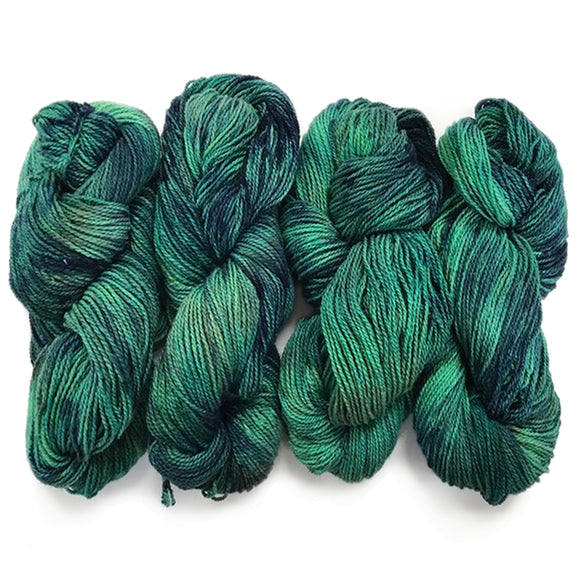 four twisted hanks of hand dyed yarn in shades of sea green and stormy grey blue the yarn has a well defined ply in silk and wool fibers