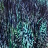 close up image if dk weight yarn in silk and wool fibers the colors of the yarn are a dark deep blue with pops of sea green-blue and seaweed green