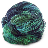 one hank of yarn piled up onto itself into a little mound the colors of the yarn are seaweed green, sea blue green, and dark stormy blue grey