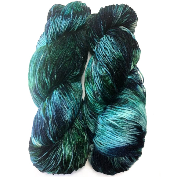 two twisted hanks of sparkly sock yarn in speckled shades of sea green blue, dark grey blue, and rich seaweed green