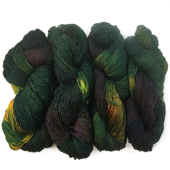 four hanks of hand dyed sock yarn lined up next to each other. They are colored mostly with a dark hunter green but feature sections of gold ochre, light green, and an intensely dark, almost black, purple