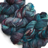 a crosscut of 4 hanks of hand dyed dk yarn arrange diagonally across the image. the blueas are deep and stormy wiht a hue of grey white the burgundy is intensely dark like a good pinot