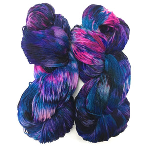 two hanks of sock yarn twisted up and positioned next to each other. They are bother dyed with lots of purple, some areas are a darker purple some are lighter purple. They features pops and specks of hot pink and fuchsia trying to break through