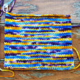 close up of our knitted swatch in carribbean party. only 4 stitches wide it has created a random color pattern in yellow, blue purple and white