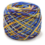 Caribbean party sock yarn has been caked up into a canter pull cake, the colors are running all which way like streamers of blue, yellow and purple