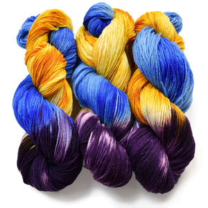three hanks of hand dyed sock yarn lined up in a row. The bottom quarter of the hank is a dark purple, and above the, bright sunshine yellow and medium cobalt blue strands wrap around eachother.