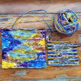 set against a wood background and looking from above we see two knit swatches of caribbean party, the left one is much larger and the colrs have formed a pattern, the right one is small and had created a totally random arrangement of colors in yellow blue and purple. The caked yarn sits in the top right corner looking suspicious