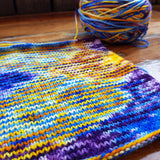 looking sidelong at our planned color pooling swatch, and band of yellow stitches marches towards us, while the caked yarn in the background eggs them on