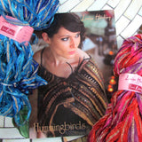 the front cover of louisa hardings hummingbirds knitting pattern book with a woman wearing a knitted black and gold feathered shawl. next to the book is two glittering hanks of louisa hardings sari ribbon