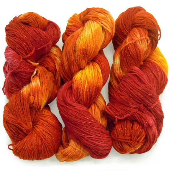 Three hanks of hand dyed yarn in bright red, orange and a little bit of yellow with some silver sparkle form metallic tinsel spun into the strand