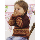 jam sandwich pullover knitting pattern from louisa hardings enchanted garden book. a little boy sits wearing a pullover knit sweater with fair isle pattern around cuffs and waist