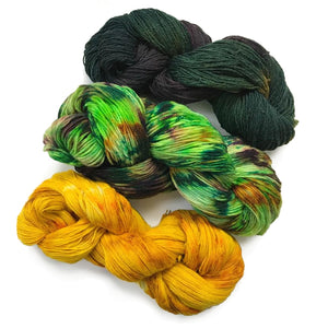 image of three twisted hanks fo yarn presented diagonally across the image. the lower one is bright yellow, middle hank is highly speckled in shades of bright jungle green, dark fern green and pops of golden ochre. the top hank is in shades of really dark hunter green which blends in a very dark royal purple