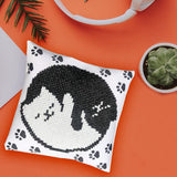 image of a miniature pillow on orange backgrounds surrounded by plants. the design on the pillow looks like a ying yang symobol made up of a black cat and white cate snuggling together. The background design on the pillow is white with black pawprints.