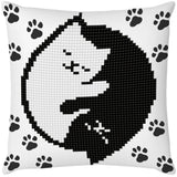 image of a white pillow printed with black pawprints all over. the main central design on the pillow is two jewel encrusted cats one black and one white, sleeping together in a circle reminiscent of a yin yang symbol