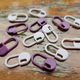 knit picks locking stitch markers in light and dark purple set against a wood background
