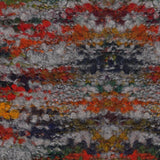 knitted swatch of lana gatto's belleveu yarn looks like a  low pile rug in colorway greys 8836 a base of medium grey with pops of orange, red, blue, and mustard