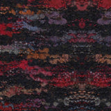 knitted swatch of lana gatto's belleveu yarn looks like a  low pile rug in colorway blacks 8840 a base of very dark grey with pops of red, blue, purple and orange