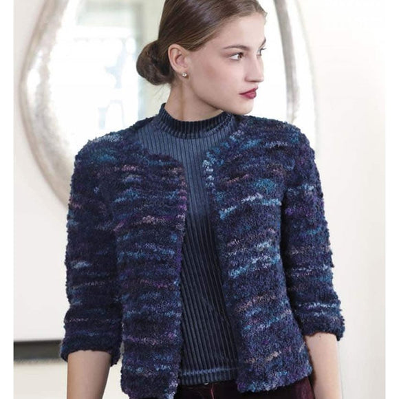 woman wearing a knitted jacket which is open att eh front, features ⅝ length sleeves and is knitted with bellevue yarn in shade of blue giving it a soft tapestry effect