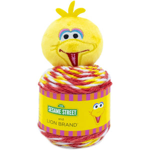 image of one ball of yarn topped by a plush big bird stuffed toy for adorning the top of a hat or snuggly cloth, the yarn is colors of red yellow and white