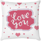 image of a white pillow with pink hearts. in the center of the pillow is a pink beaded cloud shape which says 'love you' in silvery sparkly diamonds