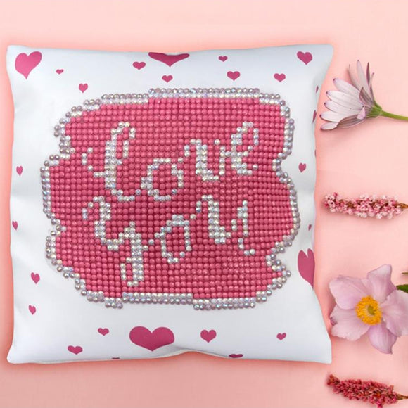 image of a white pillow wiht pink hearts on a pink background with flowers next to it. large, on the face of the pillow is a pink diamonte shape with 'love you' written in silver sparkles