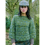 woman in the forest wearing a green short sweater with 3/5 length sleeves and horizontal stitch details knitting pattern from Louisa Harding's Wildspur Knitting Patterns book