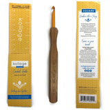 one kollage square crochet hook is positioned vertically in the middle of two views of the packaging it comes in. to the left is the front side with a build in ruler for checking you gauge, and the back of the packaging featuring information about the charitable giving kollage is now doing