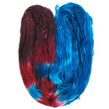 one hank of yarn layed open in a U shape the right half is a bright cobalt blue, the tip of the left secction shows a grape burgundy and then running down the left arm it has a red stripe, blue stripe and red stripe again