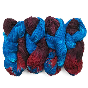 four hanks of superwash merino yarn hand painted in bright blue , crimson red and purple burgundy it appears half the hank is blue, and the other half is purple with red in between the blue and purple