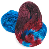 on hank of yarn spiraled up on itself, the underneath section is a bright ocean blue, the top portion has a burgundy end, and red blotches