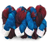 four twisted hanks laying next to each other with their labels on it appears one half of the yarn is blue, while the other half is a blend of purple burgundy and blood red