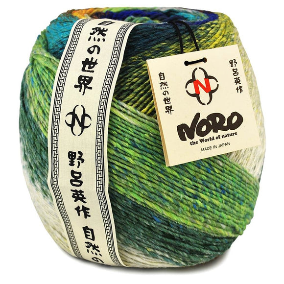 one large ball of noro tsubame bright color silk wool blend. showing lots of bright green dark green, white and little bits of blue. The noro yarn label and antique japanese writing runs along the label