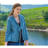 Ovingham  from Louisa Harding's Winter's Muse Landscapes Pattern Book. Showing a woman standing in front of a lake wearing a long sleeved loose cardigan with a tie in the front and large wide collar with pockets and ⅞ length sleeves