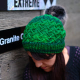close up of woman wearing a lattice crisscrossing pattern bright green slouchy beanie with black pom pom