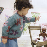 Posy sweater knitting pattern from louisa hardings enchanted garden book. a little girl is wearing a sage green knitted sweater with intarsia flowers in colors of purple pink and red, with picot edging on collar and cuffs
