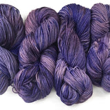 image of 4 twisted hanks next to eachother hand dyed with shades of purple lavender with light purple and dark violet with a tight play and good yarn definition