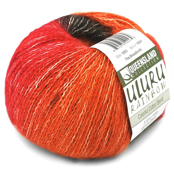 ball of uluru rainbow fingering weight yarn shown in bright orange and red with a fine halo and white strands throughout