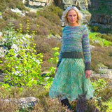 Ravenscar from Louisa Harding's Winter's Muse Landscapes Pattern Book. showing a woman out on a verdant hillside wearing a long sleeved pullover with wide ribbed cuffs and lower hem