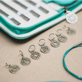 seven sterling silver round stitch markers with cut out chakra symbols