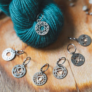 image of knitters pride chakra stitch markers  in sterling silver gaisnts a wood and dark blue yarn background