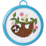image of a miniature cross stitch kit with blue round plastic frame. Cross Stitch design is of a happy brown sloth hanging from a tree branch.