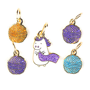 image of 5 cute charm stitch markers one id a knitting glittery unicorn and the other four are glittering balls of yarn in purple teal and gold from knit picks